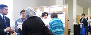 attendees discussing a poster presentation